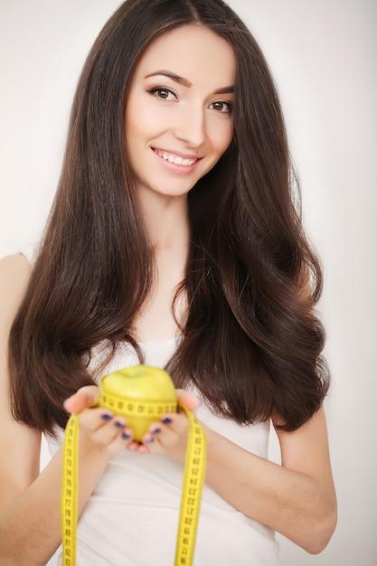 Diet, slim jeune femme mesurant sa taille avec un ruban à mesurer Photo Premium