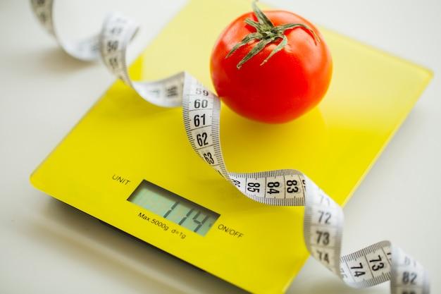 Diet, tomate avec ruban à mesurer sur une balance Photo Premium