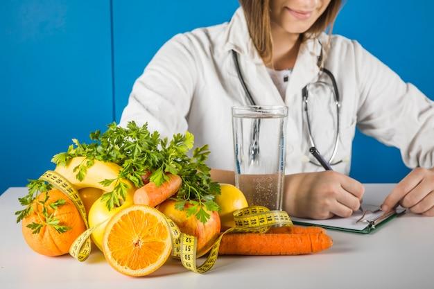 Diététicienne écrivant sur le presse-papiers avec des fruits frais sur le bureau Photo gratuit