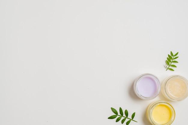 Différent type de crème hydratante avec des feuilles sur fond blanc Photo gratuit