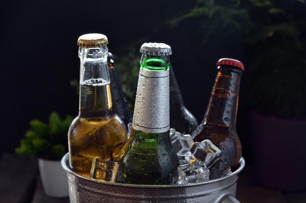 Différentes bières sur une table de bois. il y a une bouteille et un verre avec de la glace pour les garder au froid Photo Premium