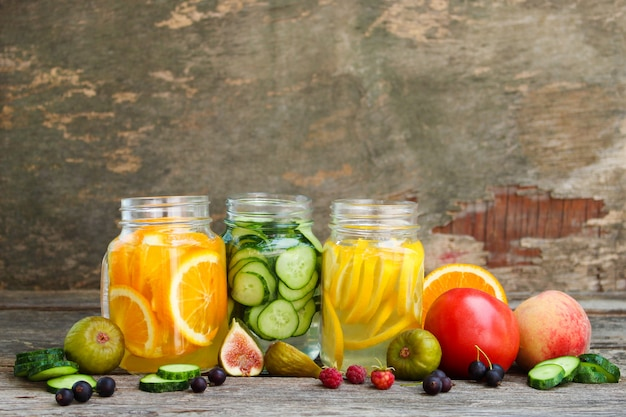Différentes boissons, fruits et légumes sur fond en bois. Photo Premium