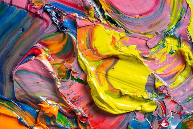 Différentes couleurs vives des peintures à l'huile sont mélangées dans une palette en gros plan. Photo Premium