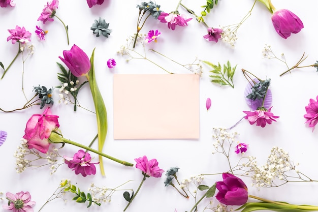 Différentes fleurs avec du papier sur un tableau blanc Photo gratuit