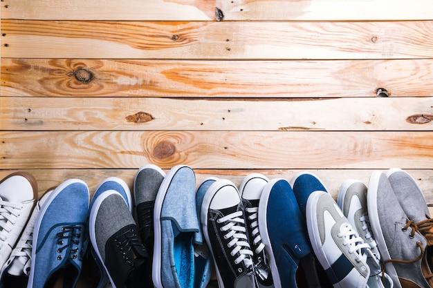 Différentes paires de baskets posées sur le plancher en bois Photo Premium