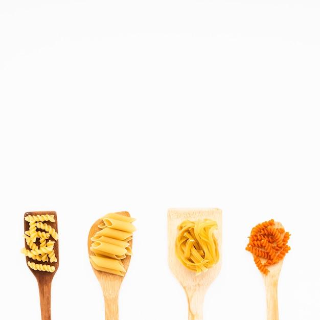 Différentes pâtes italiennes à la spatule en bois sur fond isolé Photo gratuit