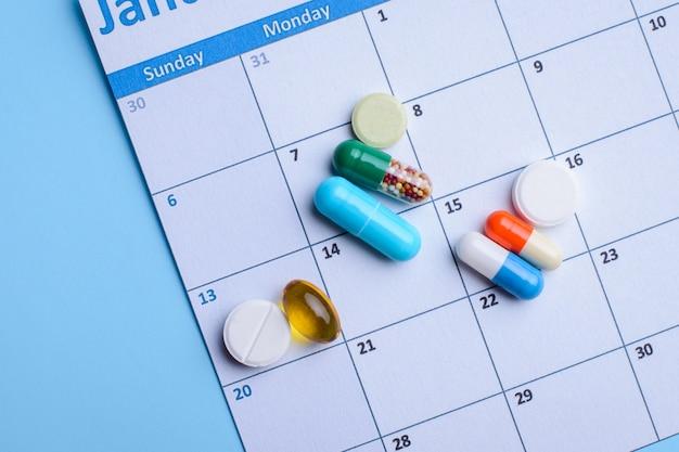 Différentes Pilules Médicales Se Trouvaient Sur Le Calendrier. Photo Premium