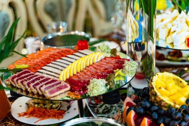 Différentes sortes de viande tranchée au citron dans une assiette sur une table de fête. assiette joliment décorée de viande et de citron sur une assiette spéciale. fermer Photo Premium