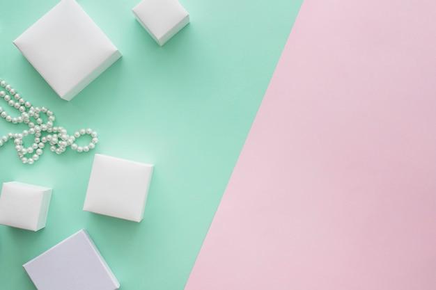 Différentes tailles de boîtes et collier de perles sur fond coloré Photo gratuit