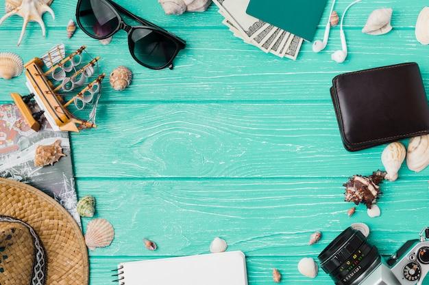 Différents accessoires parmi les coquillages et le bateau jouet Photo gratuit