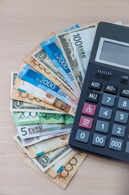 Différents billets de banque aux vertus différentes se dressent sur votre bureau avec une calculatrice Photo Premium