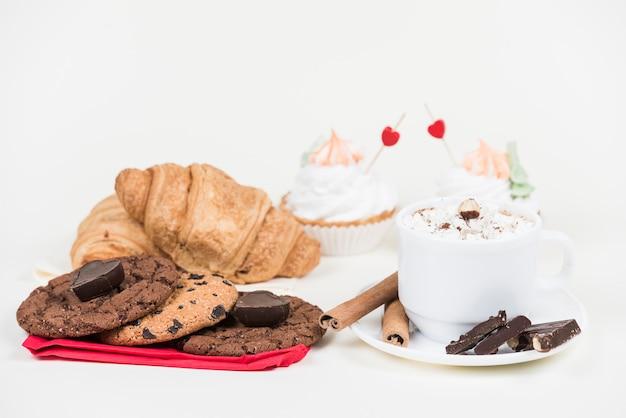 Différents bonbons avec une tasse de café sur la table Photo gratuit