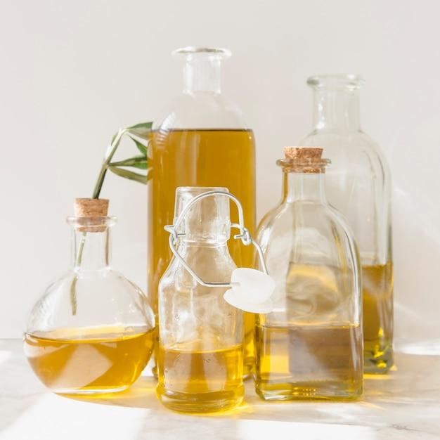 Différents flacons et bouteilles d'huile sur fond blanc Photo gratuit