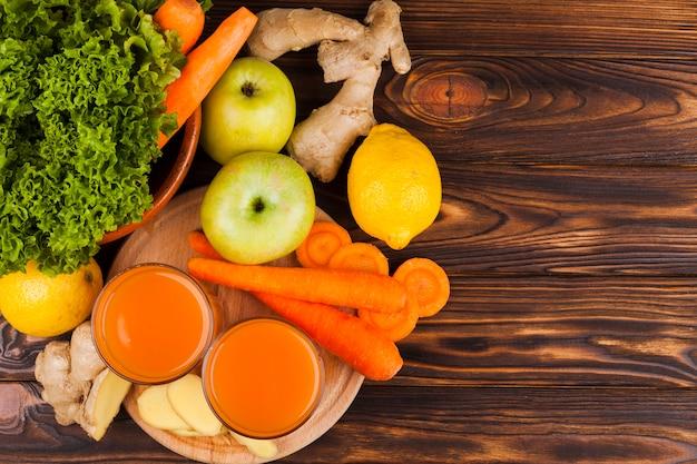 Différents fruits et légumes sur une surface en bois Photo gratuit