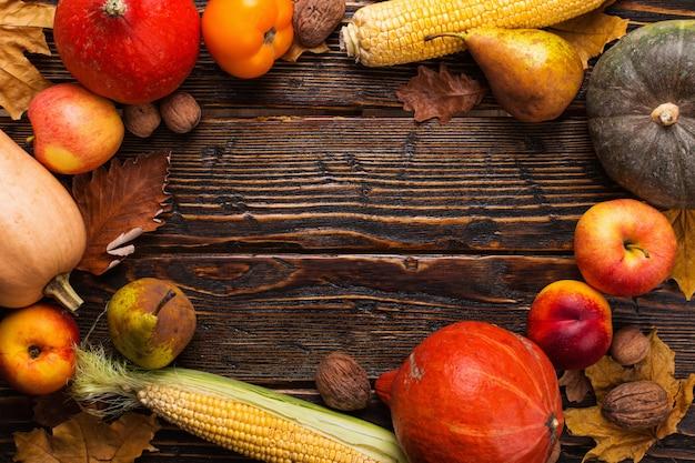 Différents légumes, citrouilles, pommes, poires, noix, tomates, maïs, feuilles jaunes sèches sur fond en bois. humeur d'automne, surface. récolte . Photo Premium