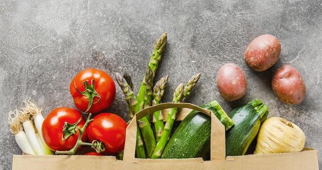 Différents légumes dans un sac en papier sur fond gris Photo gratuit