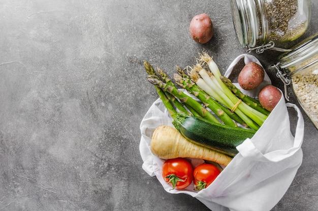 Différents légumes dans un sac en textile sur fond gris Photo Premium