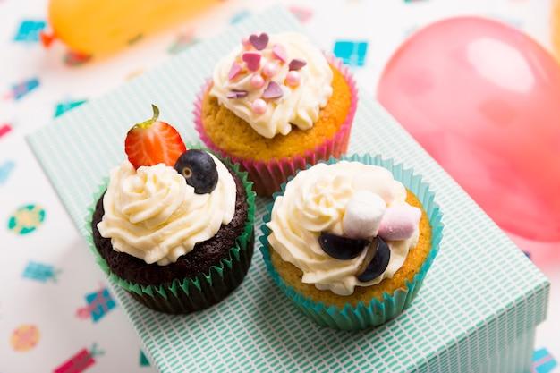 Différents petits gâteaux avec des baies sur la boîte Photo gratuit