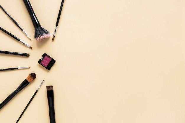 Différents pinceaux à poudre avec ombre à paupières sur une table beige Photo gratuit