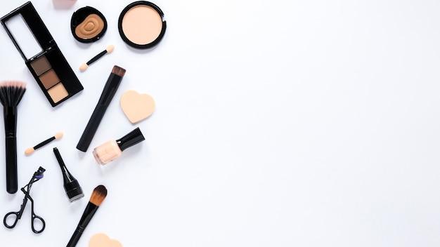 Différents produits cosmétiques dispersés sur une table lumineuse Photo gratuit