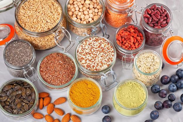 Différents superaliments aux baies de goji, quinoa, chia, graines de chanvre, graines de lin, pois chiches, avoine, amande, myrtilles, curcuma, matcha et lantilles. végétalien, végétarien, concept de produits bio régime diététique Photo Premium