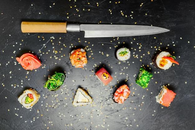 Différents sushis avec un couteau japonais sur fond d'ardoise en pierre noire. sushi sur une table. Photo gratuit