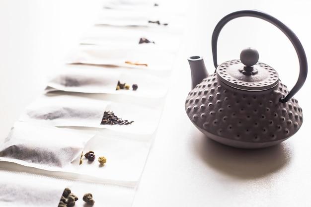 Différents thés dans des sacs filtrants jetables pour une infusion à côté d'une bouilloire en fonte grise sur fond blanc Photo Premium