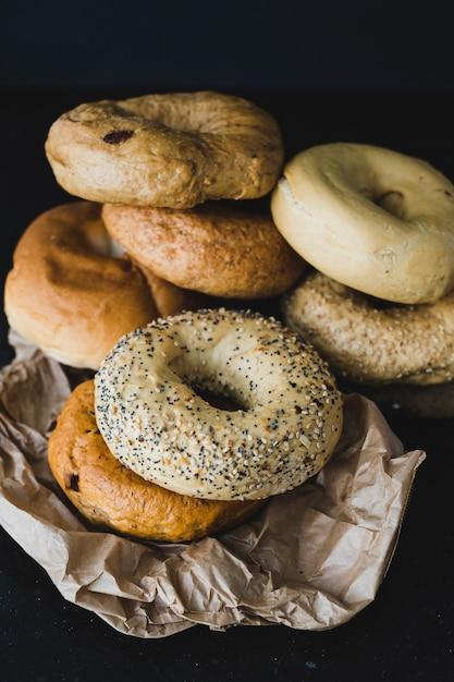 Différents types de bagels sur papier brun froissé sur fond noir Photo gratuit