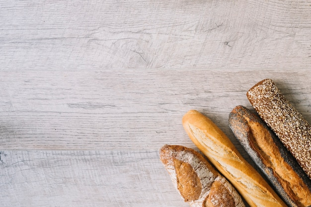 Différents types de baguettes sur fond texturé en bois Photo gratuit