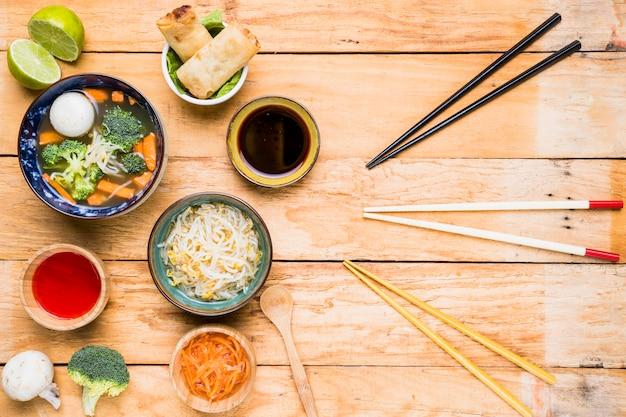 Différents types de baguettes avec des plats délicieux traditionnels thaïlandais sur un bureau en bois Photo gratuit