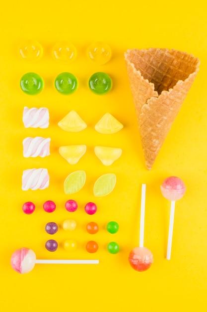 Différents types de bonbons et cornet de gaufres à la crème glacée sur fond jaune Photo gratuit