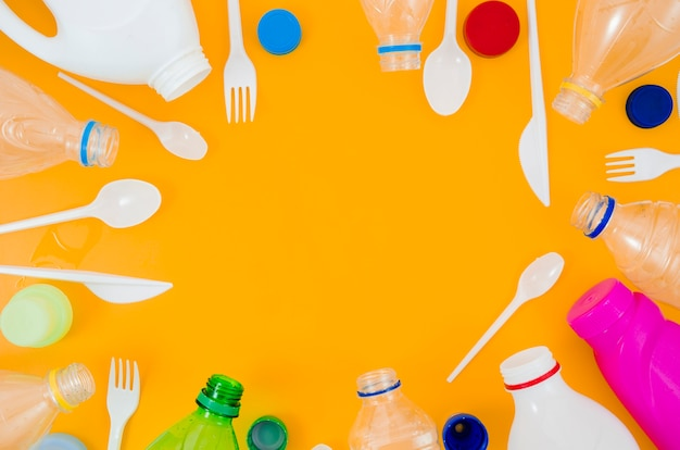 Différents types de bouteilles et de cuillères disposées dans un cadre circulaire sur fond jaune Photo gratuit