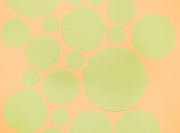 Différents Types De Cercles De Papier Vert Sur Fond Orange Photo gratuit