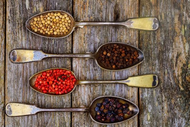 Différents types d'épices au poivre dans des cuillères vintage sur fond de bois Photo Premium