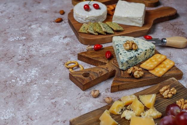 Différents Types De Fromage Sur Une Surface Brun Clair Photo gratuit