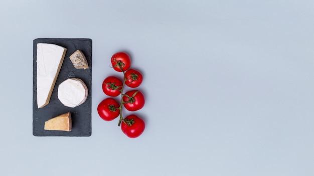 Différents types de fromages sur une ardoise noire avec des tomates rouges sur une surface grise avec espace de copie Photo gratuit
