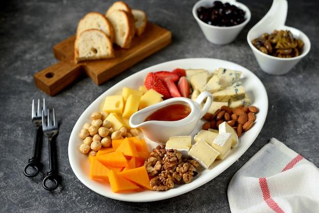Différents Types De Fromages Aux Olives, Noix, Fruits Et Miel. Apéritif Pour Une Fête Du Vin. Photo Premium