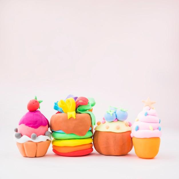 Différents types de gâteaux colorés à base d'argile sur fond rose Photo gratuit