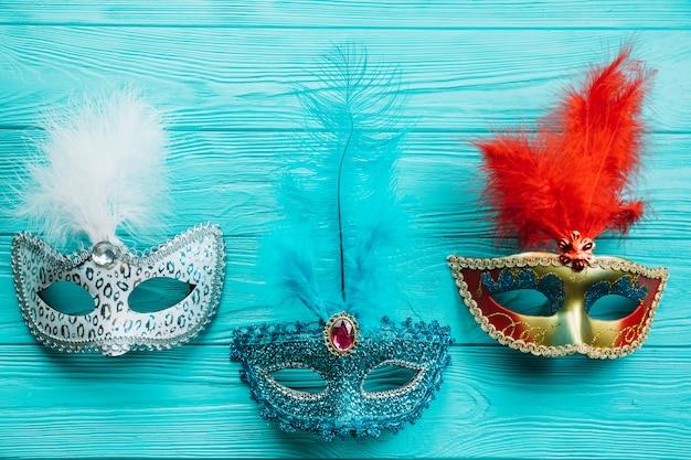 Différents types de masque de carnaval de mascarade avec plume sur une table en bois bleue Photo gratuit