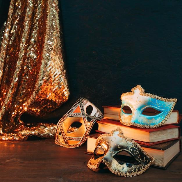 Différents types de masque de carnaval sur une pile de livres avec un tissu paillettes paillettes sur un bureau en bois Photo gratuit