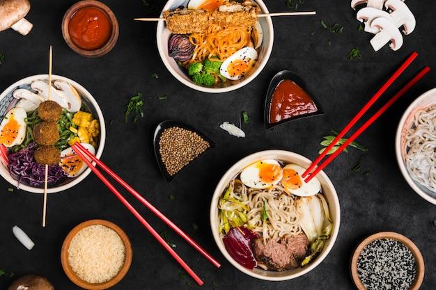 Différents types de nouilles ramen à la sauce asiatique; graines de riz et de sésame sur fond texturé noir Photo gratuit