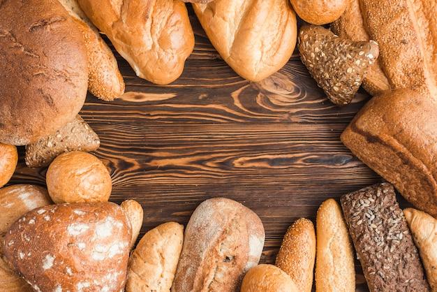 Différents types de pains délicieux sur un bureau en bois Photo gratuit