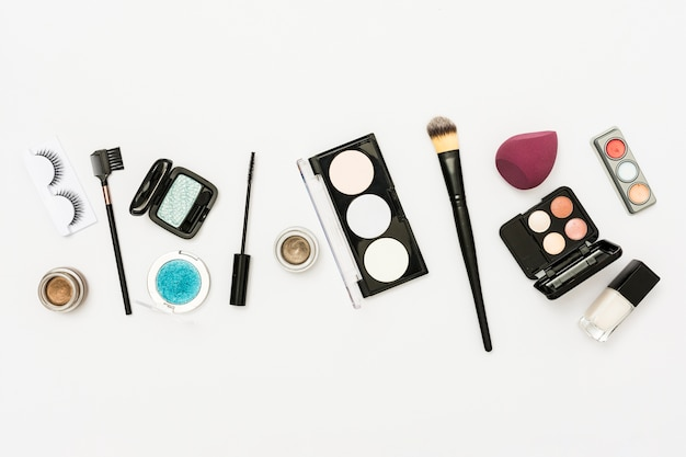 Différents types de palette de cosmétiques avec fard à paupières; bouteille de vernis à ongles et brosses sur fond blanc Photo gratuit