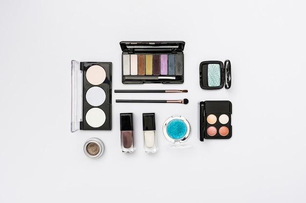 Différents types de palette de cosmétiques avec des pinceaux de maquillage sur fond blanc Photo gratuit