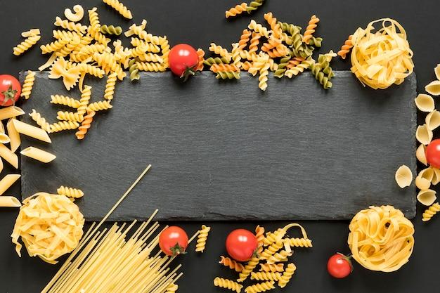 Différents types de pâtes alimentaires non cuites réparties autour de la pierre d'ardoise noire Photo gratuit
