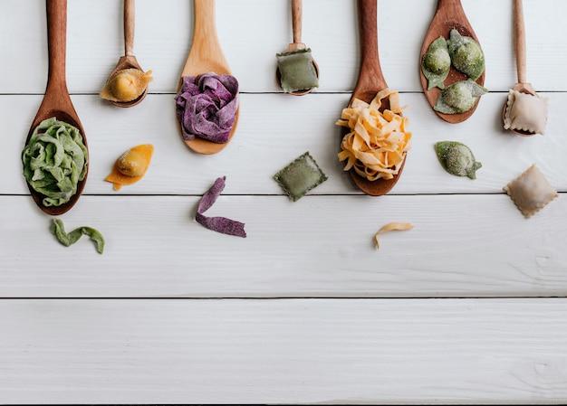 Différents types de pâtes dans des cuillères en bois sur la table. vue de dessus Photo Premium