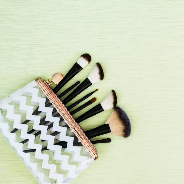 Différents types de pinceaux de maquillage dans un sac de conception transparente sur fond vert menthe Photo gratuit