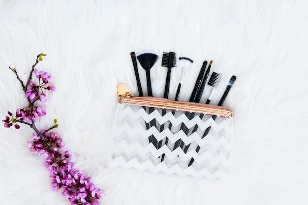 Différents types de pinceaux de maquillage dans un sac en plastique transparent avec une brindille de fleur pourpre sur une fourrure blanche Photo gratuit