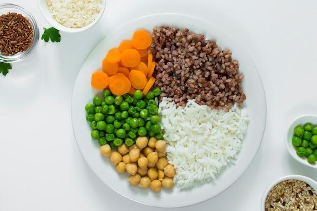 Différents types de porridge avec des légumes sur une assiette avec des bols de riz sur la table Photo gratuit