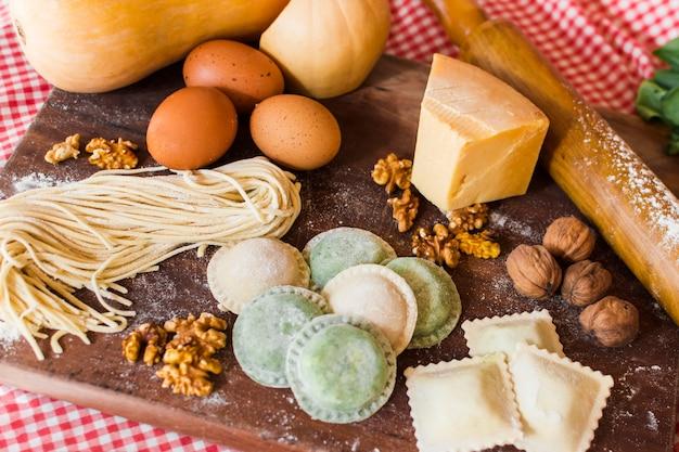 Différents types de raviolis crus avec des ingrédients sur une planche à découper en bois Photo gratuit